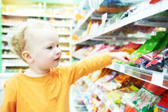 Child making food shopping at grocery store. Little child choosing sweets during food shopping in grocery store supermarket Royalty Free Stock Photography