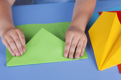 Child making a green paper plane Royalty Free Stock Image