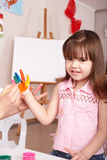 Child making hand prints. Little girl making hand prints stock image