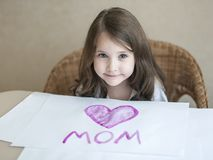 Child making homemade greeting card. A little girl paints a heart  on a homemade greeting card as a gift for Mother Day. Traditional play concept. Arts and Royalty Free Stock Photos