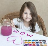 Child making homemade greeting card. A little girl paints a heart  on a homemade greeting card as a gift for Mother Day. Traditional play concept. Arts and Stock Image