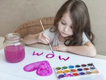 Child making homemade greeting card. A little girl paints a heart  on a homemade greeting card as a gift for Mother Day. Traditional play concept. Arts and Stock Photos