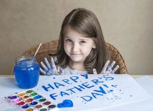 Child making homemade greeting card. Painted hand. A girl paints a heart on a homemade greeting card as a gift for Father Day. Child making homemade greeting royalty free stock image
