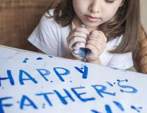 Child making homemade greeting card. Painted hand. A girl paints a heart on a homemade greeting card as a gift for Father Day. Child making homemade greeting stock images