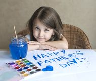 Child making homemade greeting card. Painted hand. A girl paints a heart on a homemade greeting card as a gift for Father Day. Child making homemade greeting royalty free stock photos