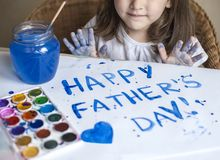 Child making homemade greeting card. A little girl paints a heart on a homemade greeting card as a gift for Father Day. Child making homemade greeting card Stock Photo