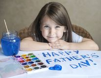 Child making homemade greeting card. Painted hand. A little girl paints a heart on a homemade greeting card as a gift. For Father Day. Finger paint. Traditional Stock Photo