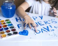 Child making homemade greeting card. Painted hand. A little girl paints a heart on a homemade greeting card as a gift. For Father Day. Finger paint. Traditional Royalty Free Stock Image