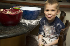 Child making a mess baking with mom stock photography