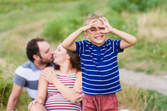Child making pretend binoculars with hands. Little boy playing with his parents. Mother is expecting a baby. Pregnant woman, husband and their son playing royalty free stock images
