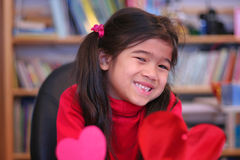 Child making red hearts Stock Photography