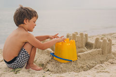 Child making sand castles at the beach. Little child making sand castles at the beach royalty free stock photos