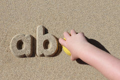 Child making sand letters on the beach Royalty Free Stock Image