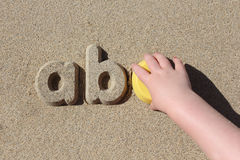 A child making sand letters on the beach Royalty Free Stock Photos