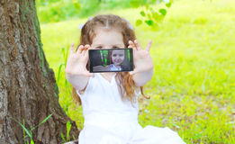 Child making self portrait on smartphone in summer park Stock Photography