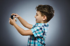 Child making selfie using a retro rangefinder camera isolated grey background royalty free stock photos