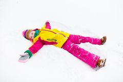 Child making snow angel. Kids play in winter park. Stock Photos