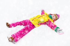 Child making snow angel. Kids play in winter park. Child making snow angel. Kids play in winter snowy park. Family Christmas vacation. Outdoor fun for children Stock Photo