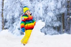 Child making snowman. Kids play in snow in winter royalty free stock photos