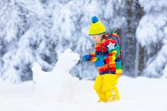 Child making snowman. Kids play in snow in winter stock photos