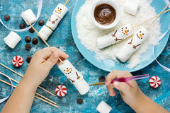 Child making snowman marshmallow pops, kitchen composition for w Stock Images