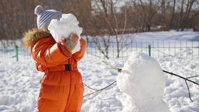 Child making a snowman in the Playground stock video