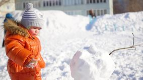 Child making a snowman in the Playground stock video footage