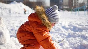 Child making a snowman in the Playground stock footage