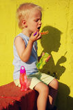 Child making soap bubbles. Little child sitting on a red concrete panel and blowing soap bubbles Royalty Free Stock Photography