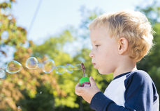 Child making soap bubbles outside Stock Images