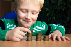Child making stacks of coins Royalty Free Stock Photo