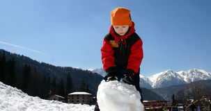 Child making a wet snow ball Stock Photos