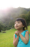 Child is making wish. Asian child is making wish at park against sunlight Royalty Free Stock Photography