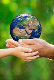 Child and man holding Earth in hands Stock Photo