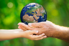 Child and man holding Earth in hands Royalty Free Stock Images