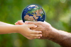 Child and man holding Earth in hands Stock Images
