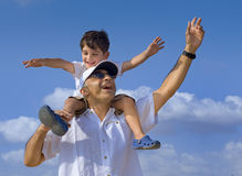 Child on man shoulders. Son riding on his father shoulders with spread arms Stock Photography
