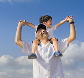 Child on man shoulders. Son riding on his father shoulders with spread arms Stock Image