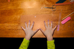 Child Manicure. A young girl's freshly manicured hands rest on a table with all of the fingernail sticker supplies close at hand Royalty Free Stock Photography