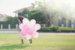 Child with many balloons running in the park under sunlight Royalty Free Stock Photography