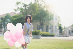Child with many balloons running in the park under sunlight Stock Image
