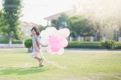 Child with many balloons running in the park under sunlight Stock Photography