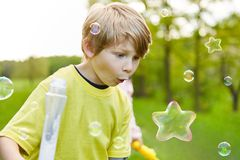 Child marvels at soap bubble in star shape stock photography