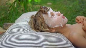 A child in a mask for the face with a snail. Snail crawling on a face mask. SPA for all.  stock footage