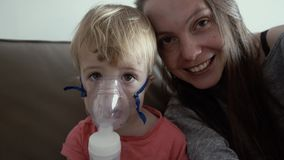 Child in a mask nebulizer. Mother hugs a sick son stock video