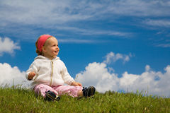 Child on a meadow. A little cute girl sits on a meadow before of a  blue easily cloudy sky Royalty Free Stock Photo