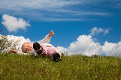 Child on a meadow. A small girl playing on a meadow before a blue easily cloudy sky Stock Image