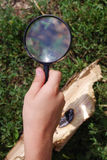 Child by means of a magnifying glass kindles fire Royalty Free Stock Photography
