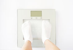 Child measures weight on scales Royalty Free Stock Image