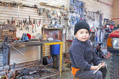 Child mechanic working in workshop Royalty Free Stock Images